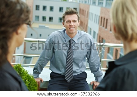 Business people talking on terrace of office building. Businessman in front, over the shoulder view. - stock photo
