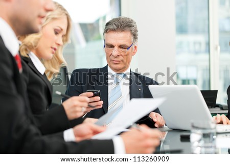 Business people - team meeting in an office, the boss is checking his mails - stock photo