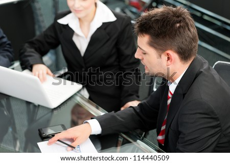 Business people - team meeting in an office with laptop - stock photo