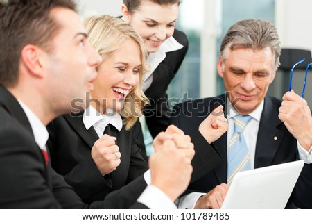 Business people - team meeting in an office with laptop, the boss with his employees is obviously successful - stock photo