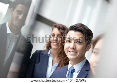 Business people team meeting in front of the office window, asian and caucasian