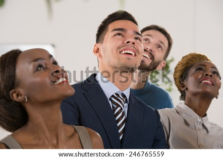 Business people team of diverse ethnicity looking up and dreaming - stock photo