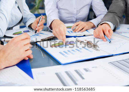 business people team work group during conference discussing financial diagram, graph, business charts, businesspeople meeting sitting at desk office point finger at graph document - stock photo