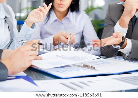 business people team work group during conference report discussing financial diagram, charts, businesspeople meeting sitting at desk office pointing hand finger at graph document - stock photo