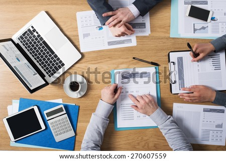 Business people team working together at office desk with laptop, tablet, financial paperwork and reports, top view - stock photo