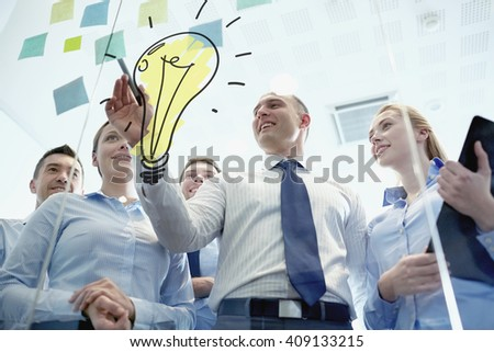 business, people, teamwork and planning concept - smiling business team with marker, stickers and light bulb doodle working in office - stock photo