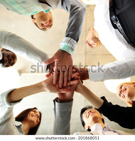 business people teamwork in an office with hands together - stock photo
