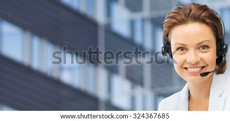 business, people, technology and communication concept - happy female helpline operator in headset over city office building background - stock photo