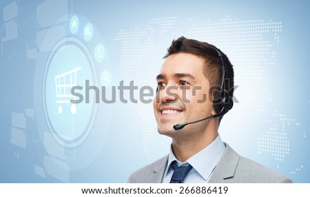 business, people, technology and customer service concept - smiling businessman in headset looking to virtual shopping trolley icon over blue background - stock photo