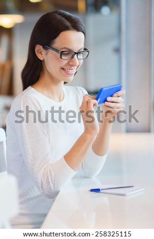 business, people, technology and lifestyle concept - smiling young woman in eyeglasses texting message with smartphone at cafe - stock photo
