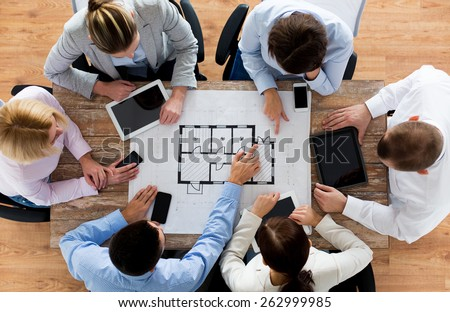 business, people, technology and team work concept - close up of architects with blueprint, smartphones and tablet pc computers sitting at table in office - stock photo