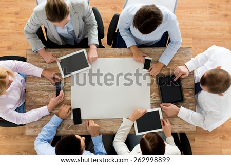 business, people, technology and team work concept - close up of creative team with, blank paper smartphones and tablet pc computers sitting at table in office - stock photo