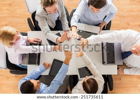 business, people, technology and team work concept - close up of creative team with laptop and tablet pc computers showing high five gesture and sitting at table in office - stock photo