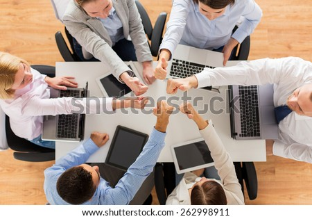 business, people, technology and team work concept - close up of creative team with laptop and tablet pc computers showing thumbs up gesture and sitting at table in office - stock photo