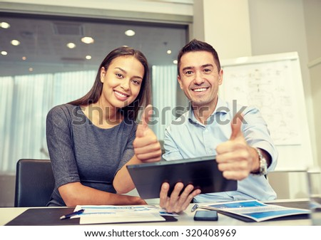 business, people, technology and teamwork concept - smiling businessman and businesswoman with tablet pc computer showing thumbs up gesture meeting in office - stock photo