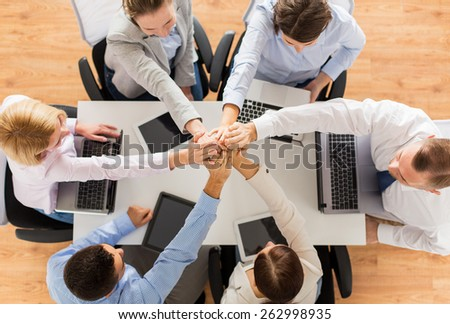 business, people, technology, cooperation and team work concept - close up of creative team with laptop and tablet pc computers sitting at table and holding hands on top of each other in office - stock photo