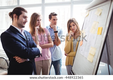 Business people thinking while looking at blueprints on board in creative office - stock photo