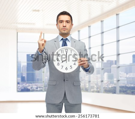 business, people, time management and gesture concept - businessman in suit holding clock showing 8 o'clock and pointing finger up over office room and window with city view background - stock photo