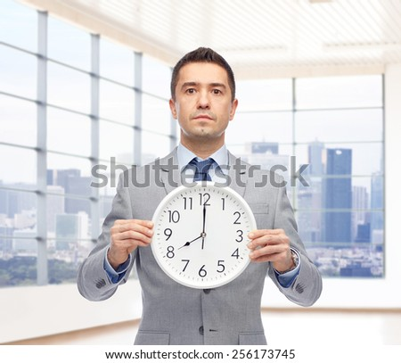 business, people, time management and office concept - businessman in suit holding clock showing 8 o'clock up over city office window background - stock photo