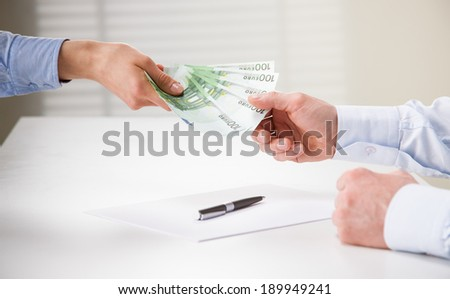 Business people transfering euro banknotes over the table - stock photo