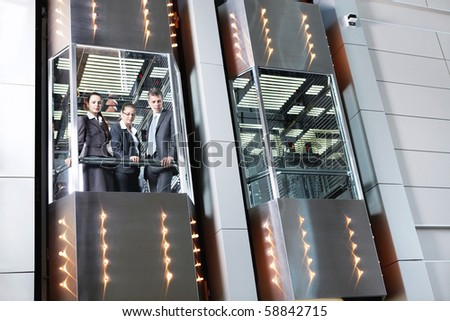 Business people traveling in the elevator looking down - stock photo