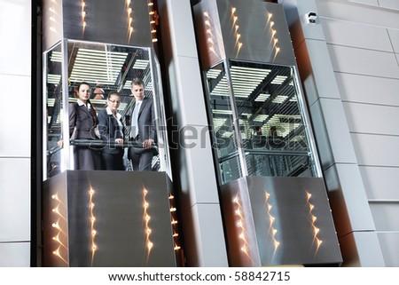 people in elevator. business people traveling in the elevator looking down