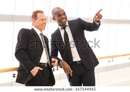 Business people. Two cheerful business men standing close to each other while one of them pointing away and smiling - stock photo
