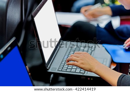 Business people typing on laptop keyboard at conference. - stock photo