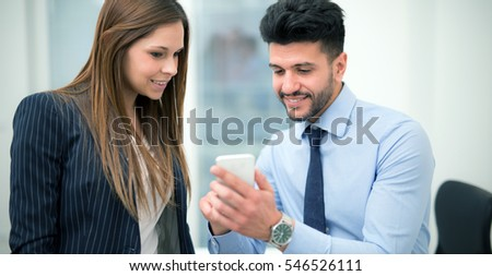Business people using a mobile phone in their office