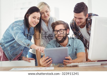 Business people using digital tablet at computer desk in office - stock photo