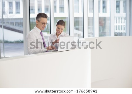 Business people using laptop on railing in office - stock photo
