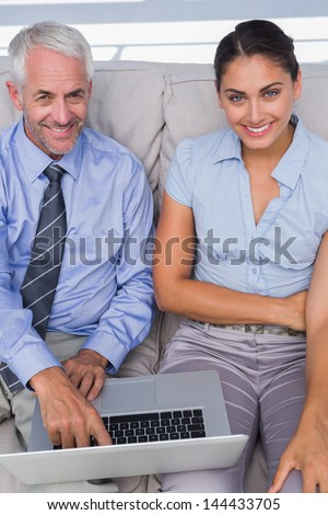 Business people using laptop on the couch and smiling up at camera in the staffroom - stock photo