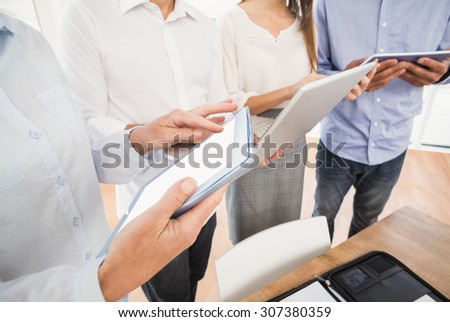 Business people using several electronic devices in the office - stock photo