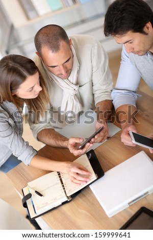 Business people using smartphone in meeting