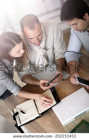 Business people using smartphone in meeting - stock photo