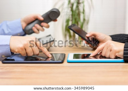 business people using tablet computers during meeting and using phones for communication - stock photo