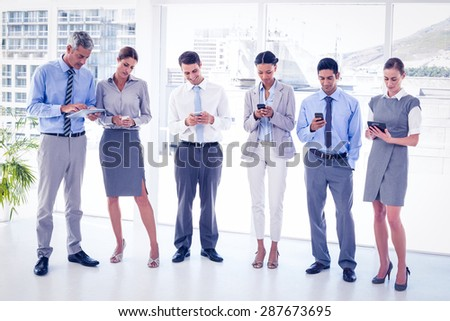 Business people using their phone in office - stock photo
