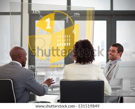 Business people using yellow pie chart interface in a meeting - stock photo
