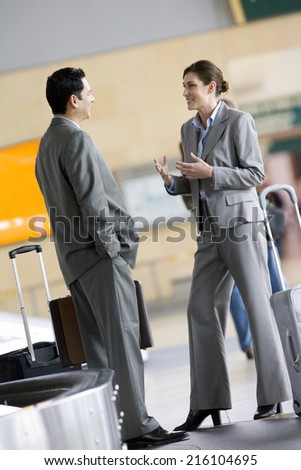 Business people waiting for luggage in baggage claim - stock photo