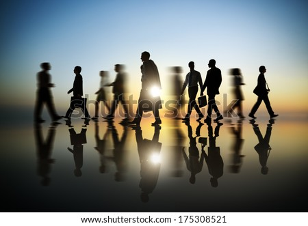 Business People Walking at Sunset - stock photo