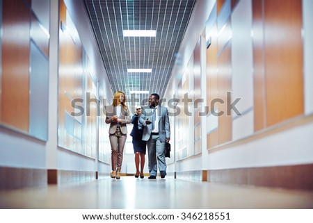 Business people walking down the office corridor and communicating - stock photo