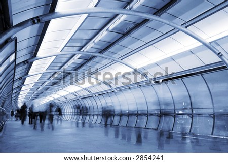 Business People walking in a futuristic tunnel. Shot with slow shutter speed to create blur effect - stock photo