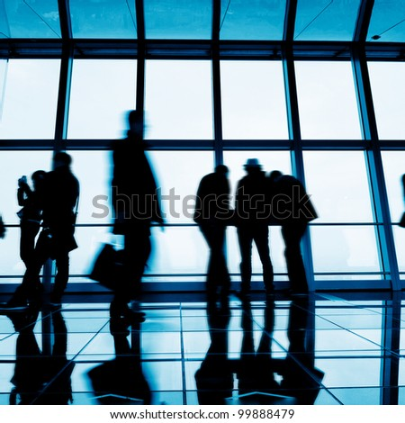 Business people walking in the aisle of the office building - stock photo