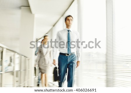 Business people walking in the office corridor, blurred motion - stock photo