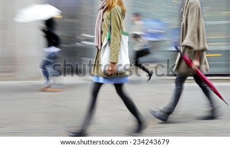 business people walking in the street on a rainy day motion blurred - stock photo