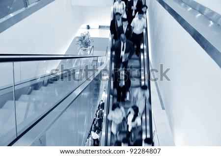 Business people walking on escalator.Blurred motion - stock photo