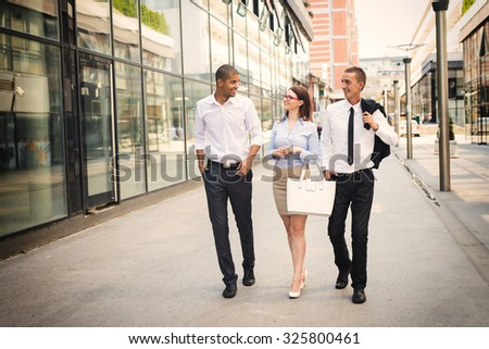 Business people walking trough passage, looking each other and smiling. - stock photo