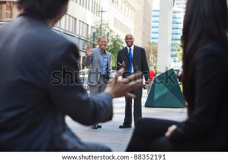 Business people waving and greeting friends on street - stock photo