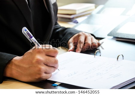 Business people who work hard and are signing the document.