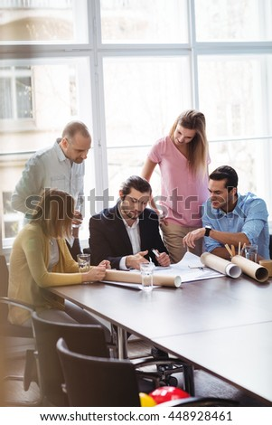 Business people with blueprint in meeting room at creative office - stock photo
